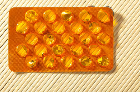 pill popping: Closeup of orange package of pills tablets drug medicine as background  Health and addiction