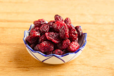 cranberry fruit: Healthy food organic nutrition  Dried cranberries cranberry fruit in bowl on wooden table background Stock Photo