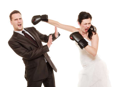 Bad relationship- conflict. Funny married couple fighting. Wife showing her husband whos boss. Angry woman bride in wedding dress boxing punching man groom isolated on white photo