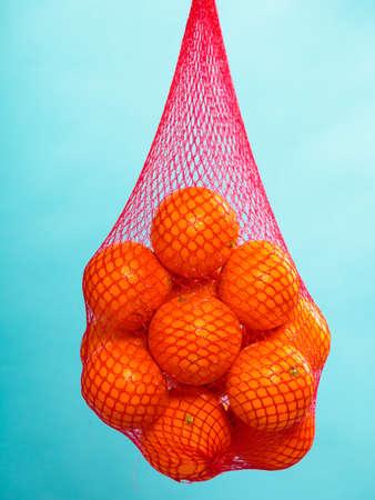 Mesh zak van verse sinaasappelen gezonde tropische vruchten van supermarkt op blauwe Foodretail