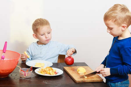 poco: Hermanos rubio niños niños niños preescolares con cocina de corte de manzana fruta cuchillo