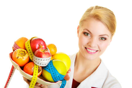 Woman in white lab coat holding fruits and colorful measure tapes isolated  Doctor dietitian recommending healthy food  Diet