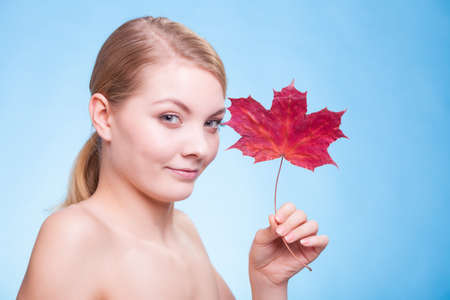 wellfare: Skincare habits. Portrait of young woman with leaf as symbol of red capillary skin on blue. Face of girl taking care of her dry complexion. Studio shot. Stock Photo