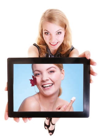 Happy blond girl showing pad with photo of woman with red leaf and moisturizing cream. Modern young businesswoman holding tablet touchpad recommending care of dry skin. Isolated. Technology and beauty. photo