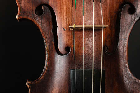 stringed instrument: Closeup of old wooden violin stringed instrument on dark gray.  Stock Photo