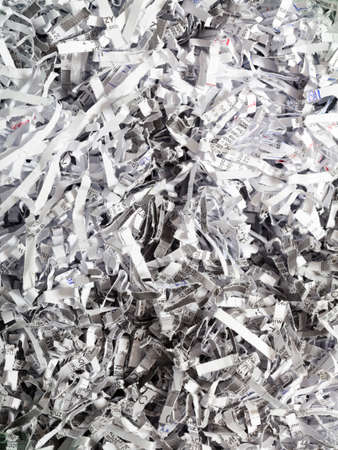 Closeup of shredded white paper with text as abstract background or texture photo