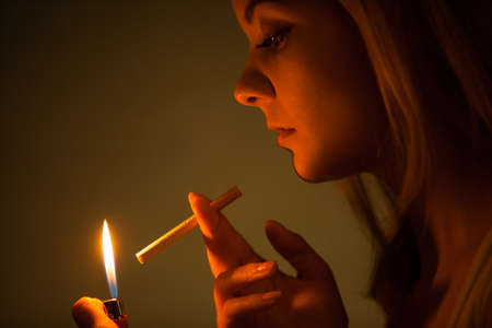 fag: Young woman with lighter lighting up cigarette.
