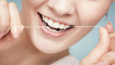 Young woman smiling girl cleaning her white teeth with dental floss on blue photo