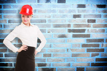 Portrait of attractive female engineer. Woman architect in red safety helmet on brick wall with blank copy space. Building. photo
