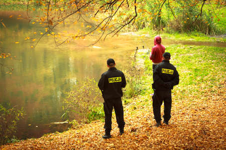 Polish police officers checking fisherman in autumnal park Fishing inspection Law
