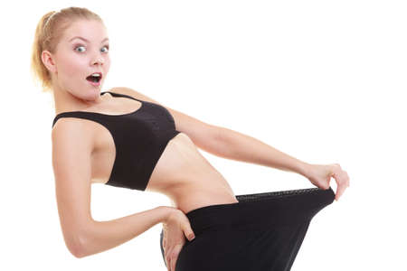 Weight loss, healthy lifestyle. Blonde young happy excited woman fitness girl with big pants, showing how much weight she lost Stock Photo