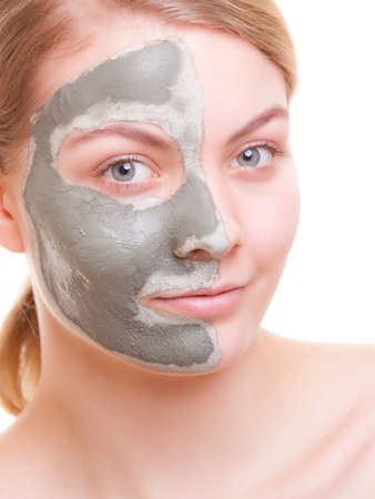 Skin care  Young woman applying clay mask on her face  Girl taking care of her dry compexion  Isolated  Spa and beauty treatment  写真素材