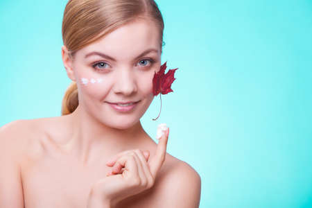 Skincare habits  Face of young woman with leaf as symbol of red capillary skin on turquoise  Girl taking care of her dry complexion applying moisturizing cream  Beauty treatment  photo