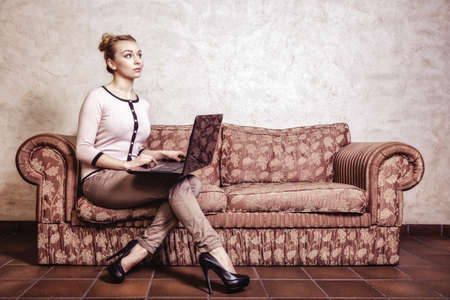 Technology internet modern lifestyle concept. Full length thoughtful business woman or student girl using laptop working on computer sitting on retro couch. Indoor. Vintage photo. photo