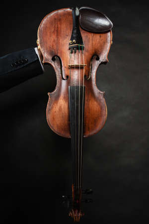 Art. Closeup of old wooden violin stringed instrument on dark gray. Classical music. photo