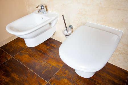 physiological: Higiene y necesidades fisiol�gicas. Primer plano de bid� de porcelana blanca y wc. Interior del cuarto de ba�o.