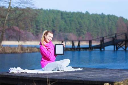 Full length of fitness woman sport teenage girl in pink tracksuit showing blank copy space screen of tablet touchpad computer sitting on pier outdoor. Electronic technology.