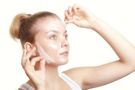 Portrait of girl young woman in facial peel off mask isolated on white  Peeling  Beauty and body skin care  Studio shot  photo