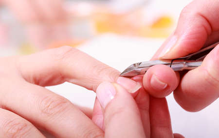 Close up of hands  Beautician trimming cuticles of female client  Manicure and skincare  Woman in spa beauty salon  photo