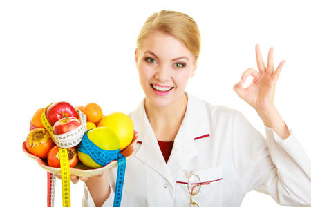 recommending: Woman in white lab coat holding fruits and colorful measure tapes isolated. Doctor dietitian recommending healthy food showing ok okay hand sign gesture. Diet.