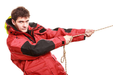 yacht isolated: Young man sailor wearing red waterproof wind jacket pulling the rope isolated on white. Sailing yachting cruise. Studio shot. Stock Photo