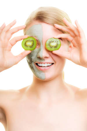 wellfare: Skin care. Woman in clay mud mask with kiwi fruit on face isolated. Girl taking care of dry complexion.