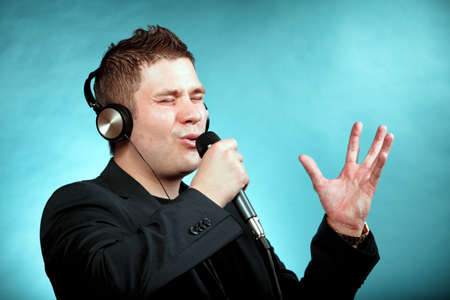 signer: Young man singing into microphone  Happy karaoke signer studio shot blue background