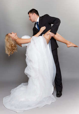 Wedding day  Portrait of happy married couple sexy blonde bride and groom in full length studio shot on gray background photo