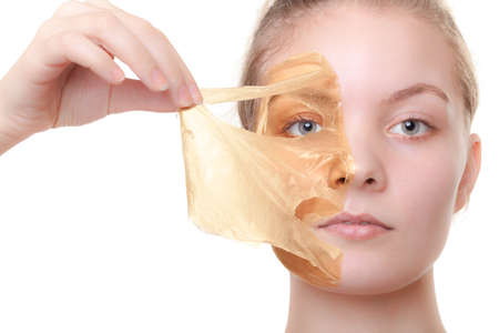 Portrait of girl young woman in orange facial peel off mask isolated on white  Peeling  Beauty and body skin care  Studio shot  photo