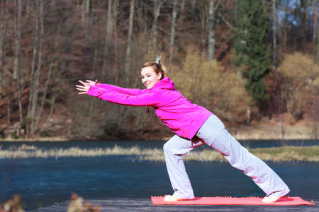 Full length of young woman teenage girl in pink tracksuit doing morning exercise on mat on pier outdoor  Healthy active lifestyle  photo
