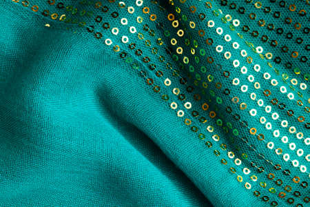 Green shiny sequine background texture abstract cloth wavy folds  Elegant sequined sparkling textile close up photo