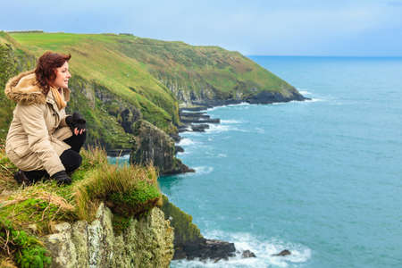 co cork: Woman sitting on rock cliff watching the ocean looking to sea. Co. Cork Ireland Europe Stock Photo