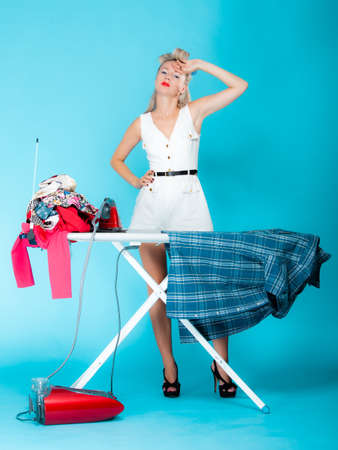Full length sexy girl retro style ironing male shirt, woman housewife in domestic role. Traditional sharing household chores.  Pin up housework.  Vivid blue background photo