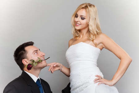 Wedding day. Portrait of romantic married couple blonde bride and enamored groom giving a rose to girl. Studio shot gray background