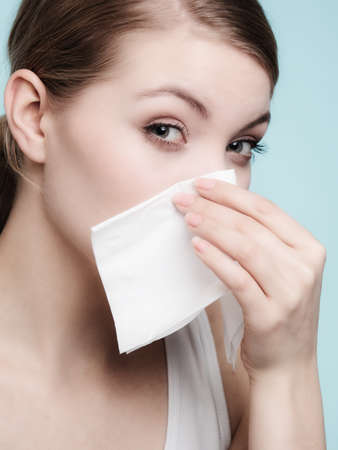 Flu cold or allergy symptom  Sick woman girl sneezing in tissue on blue  Health care  photo
