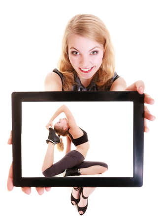 Happy blond girl showing touchpad with photo of fitness fit woman doing stretching exercise   photo