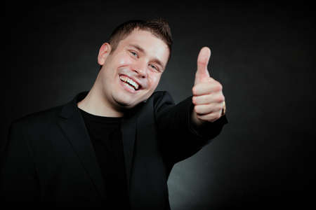 Happy man giving thumb up gesturing the all right symbol , ok sign black background photo