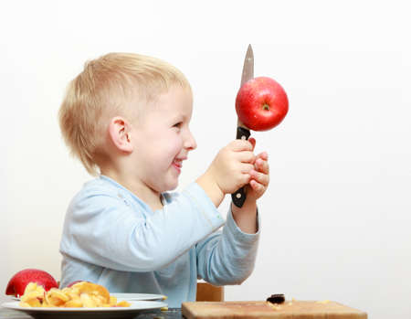 Blond boy child kid preschooler with kitchen knife cutting fruit apple at home  Happy childhood  photo
