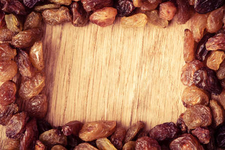 Healthy food organic nutrition. Border frame of raisin on wooden table background photo