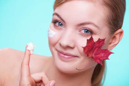 capillary: Skincare habits  Face of young woman with leaf as symbol of red capillary skin on turquoise  Girl taking care of her dry complexion applying moisturizing cream  Beauty treatment
