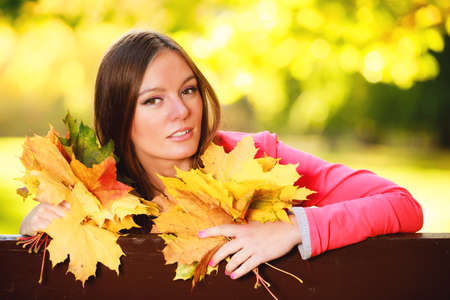 Fall season  Portrait of happy girl young woman holding colorful leaves sitting on bench in autumnal park forest  Outdoor