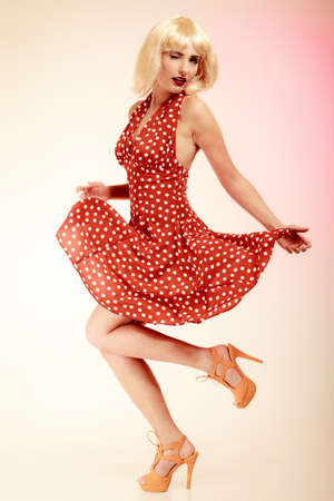 Vintage pinup style  Full length of stylish woman dancing  Girl in blond wig and retro spotted red dress on pink  Disguise  Party