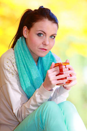 Happiness carefree and nature  Young happy woman relaxing in the autumn park enjoying hot drink coffee or tea, holding red mug with warm beverage  Yellow leaves background photo