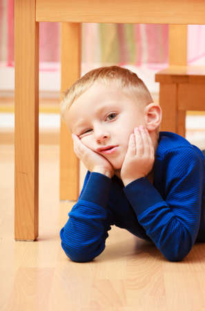 bad manners: Childhood  Portrait of pensive or tired or moody boy child kid son preschooler lying on the floor  Emotions  At home   Stock Photo