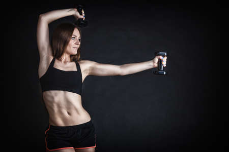 dumb bells: Fitness girl fit woman lifting dumbbells weights doing exercise with dumb bells training shoulder muscles gray background