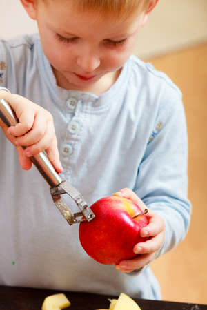 Blond boy child kid preschooler peelings fruit apple at home  Happy childhood  photo