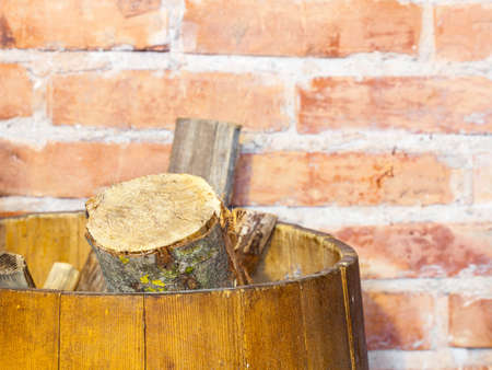 Winter at home. Closeup of reserve of firewood in the wooden barrel. Heating and fireplace. photo