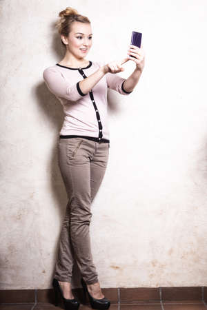 Full length of businesswoman texting on the mobile phone. Woman reading sms on smartphone. Girl taking photo of herself.  Indoor. photo