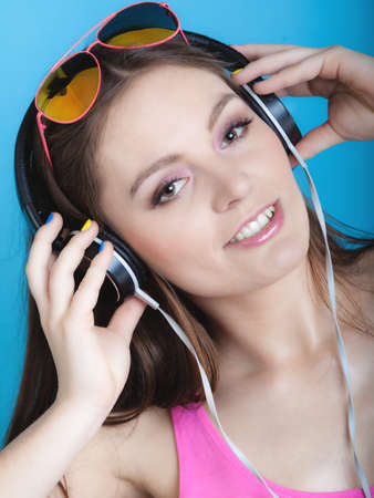 Fashion teen girl headphones listen music mp3 player, Fresh energetic young woman relax happy and dancing blue background photo