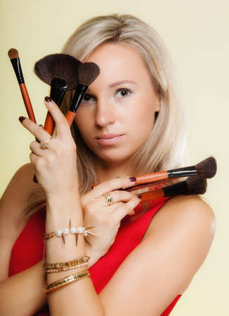 makeover: Cosmetic beauty procedures and makeover concept. Attractive woman red dress holds makeup professional brushes near face. Make-up applying with accessories tools. Yellow background